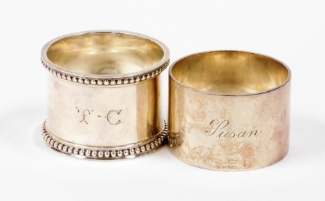 Two silver napkin rings, to include one with floral design border bearing the initials TC, Sheffield 1908, together with another of plain design stamped Lusam, Sheffield 1947, 4oz. (2)
