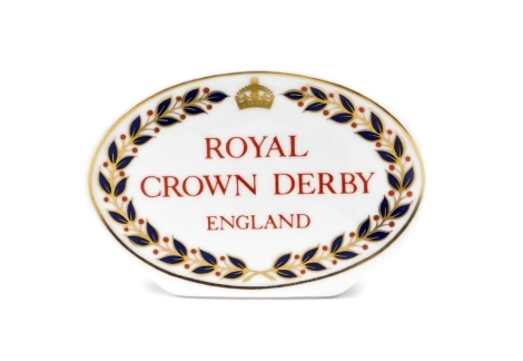 A Royal Crown Derby retailers' plaque, oval with red Royal Crown Derby England stamp to centre, 10.5cm wide.