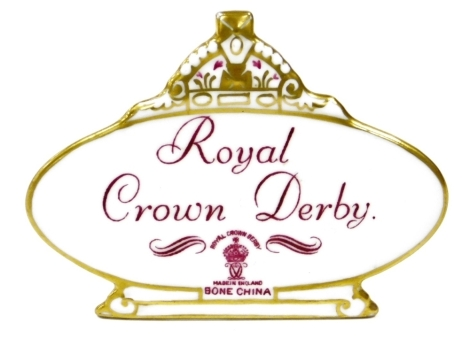 A Royal Crown Derby retailers' plaque, with crown top on an oval plaque with purple stamp and writing, 10cm wide.
