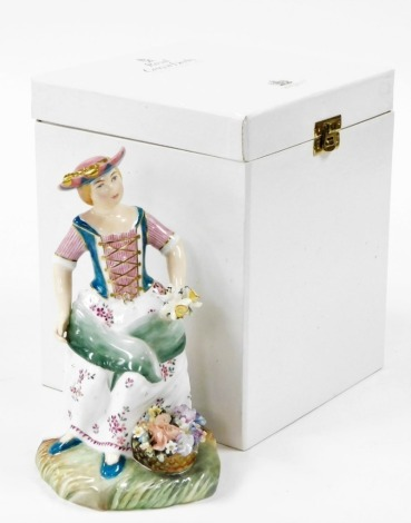 A Royal Crown Derby boxed figure of The Flower Seller, in flowing dress holding daffodils, signed J Bryan, LVII, 20cm high, boxed with certificate.