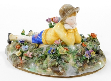 A Royal Staffordshire figure group, of a boy lying in flower garden, modelled by Bagley, with green stamp to underside and partially rubbed label, 24cm wide.