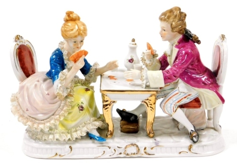 A Continental porcelain figure group, of card players in 18thC dress seated at a table, 26cm wide.