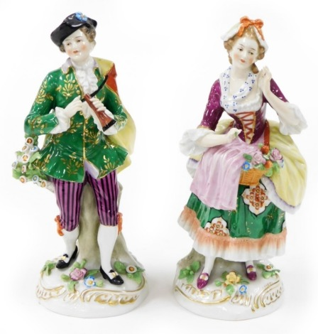 Two Continental porcelain figures, depicting a lady and gentleman each elaborately dressed, with encrusted flowers, with gold anchor mark to reverse, 24cm high.