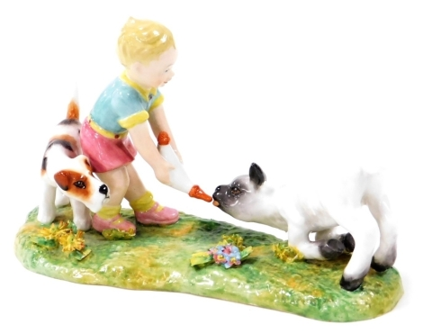 A Royal Crown Derby figure group, of a child feeding a lamb with dog, with red stamp to underside, 16cm wide.