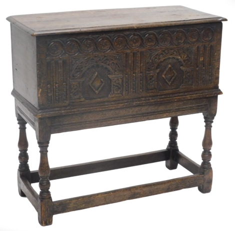 An oak chest, the rectangular top with a moulded edge above an elaborately carved frieze of arches, roundel's, lozenges, etc., the base with turned supports, 76cm high, 80cm wide, 36cm deep.