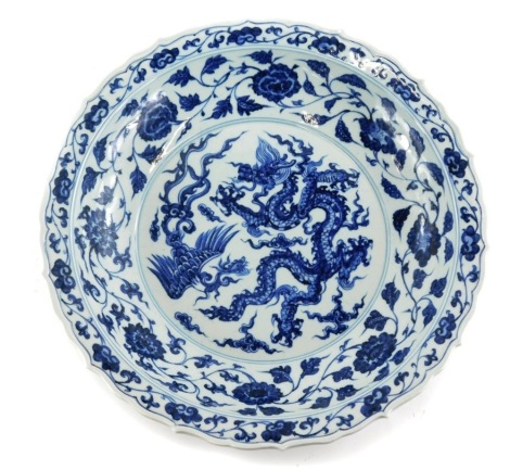 A Chinese blue and white charger, with a shaped edge decorated in blue with dragon, six character mark to underside, 42cm diameter.
