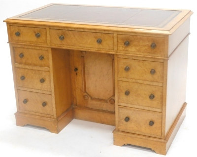 A 19thC birdseye maple pedestal desk, the top with a brown leather border, above an arrangement of nine drawers surrounding a panelled door, 74cm high, 105cm wide.