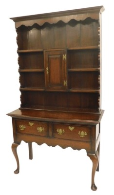 An oak dresser in 18thC style, the top with a raised border above three plate shelves, the base with two drawers, on cabriole legs with pad feet, 107cm wide.