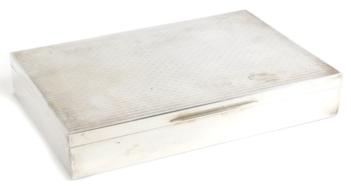 An early 20thC white metal cigarette box, of rectangular form with engine turned decoration, the hinged lid revealing a three sectioned hardwood interior, marked 926, 4cm high, 22cm wide, 15cm deep.