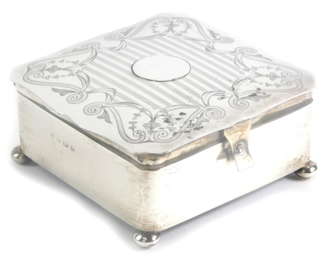 A George V silver jewellery or trinket box, of square form, the top with a shaped edge and a circular vacant cartouche and engine turned decoration, engraved with scrolls, swags, etc., the hinged lid revealing a padded satin lined interior, on four bun fe