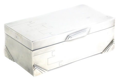 A George V silver cigarette box, of Art Deco design, with engine turned decoration and engraved monogram to lid for E.R.F., the opening and lower corners similarly decorated with layered geometric designs, the hinged lid revealed a two section treen inter