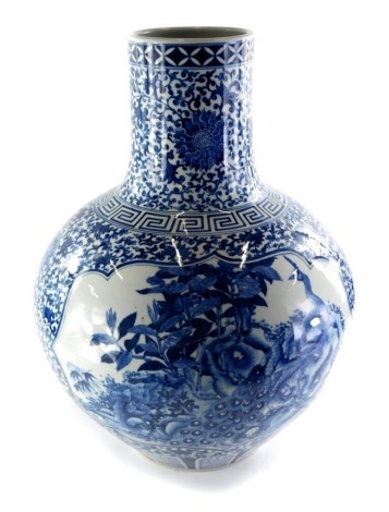 A late Chinese blue and white porcelain bottle shaped vase, decorated with birds, butterflies, flowers, etc., in blue, and hardwood stand, 65cm high overall.