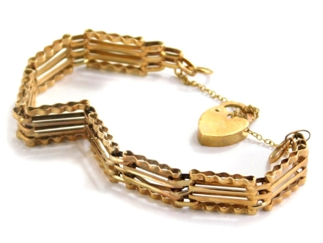 A 9ct gold gate bracelet, with four bar design and waved detail for the bottom links, with padlock and safety chain, 14cm long, 6.4g.