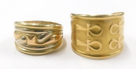 Two dress rings, to include a tri colour moulded dress ring, stamped 750, ring size P, and another Egyptian style dress ring, yellow metal, unmarked, 6.6g all in. (2)