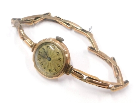A 9ct gold cased ladies wristwatch, the small circular gold coloured dial with blue hands in a 9ct gold case, on expanding bracelet, 12.2g all in.