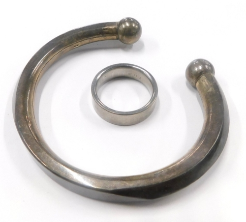 Two items of jewellery, to include a taupe bangle, white metal stamped 925, together with a gents Titanium signet ring. (2)
