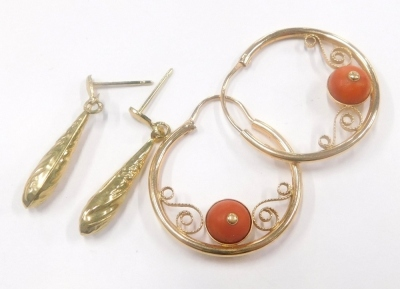 Two pairs of 9ct gold earrings, to include a pair of 9ct gold hoop earrings, each set with single coral bead and another pair of drop earrings, with floral scroll design, 4.6g all in. (2)