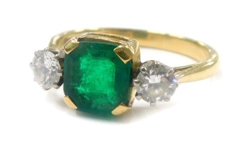 A dress ring, with central square cut green stone, in claw setting, flanked by two round brilliant cut stones, testing as moissanite, on a yellow metal band, marked but rubbed 18ct plat, ring size Q½.