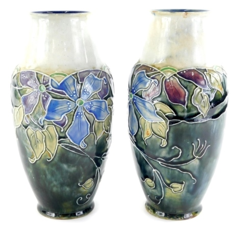 A pair of early 20thC Royal Doulton stoneware vases, tube lined with flowers on a mottled blue ground, number 8075C, impressed lion and crown marks beneath, 24cm high. (2)