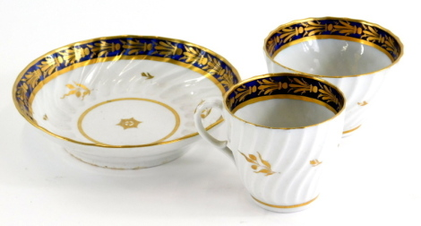 A late 18thC English porcelain trio, comprising tea bowl, saucer and tea cup, 6cm high, each in ribbed pattern with an interior gilt and floral border and outer floral sprays, unmarked. (3)