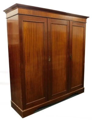 An Edwardian mahogany triple wardrobe, with a moulded cornice and a partly fitted interior, on bracket feet, 198cm high, 190cm wide.