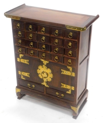 A Chinese hardwood and brass side cabinet, with an arrangement of small drawers and two doors, each with strap hinges on bracket feet, 61cm wide.