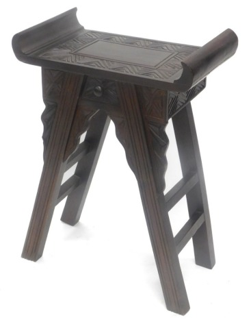 An oriental hardwood stool, the shaped top with carved seat above a small drawer on square section legs with brackets, 52cm wide.