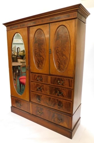 An Edwardian mahogany boxwood strung and satinwood cross banded compactum wardrobe, with top with a moulded and Greek key inlay, above an arrangement of two doors with oval panels enclosing a vacant interior, above two short and three long drawers, flanke