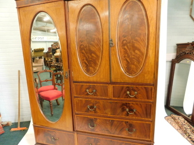 An Edwardian mahogany boxwood strung and satinwood cross banded compactum wardrobe, with top with a moulded and Greek key inlay, above an arrangement of two doors with oval panels enclosing a vacant interior, above two short and three long drawers, flanke - 2