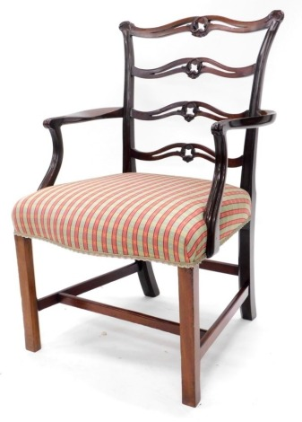 A mahogany open armchair in George III style, with a pierced carved ladder back, shaped arms and a padded seat, upholstered in check patterned fabric on chamfered legs with H stretcher.