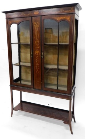An Edwardian mahogany marquetry display cabinet, the top with a moulded cornice with two astragal glazed doors enclosing a fitted interior on splay legs with under tier. (glass AF) 170cm high, 106cm wide.