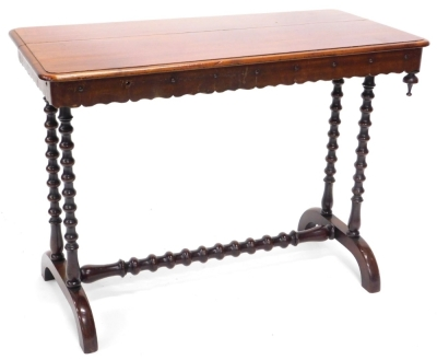 A Victorian mahogany library table, the rectangular top with a moulded edge and a crenellated frieze with drop finial, on twin bobbin turned supports with central stretcher and splayed feet, (AF), 67cm high, 91cm wide, 45cm deep.