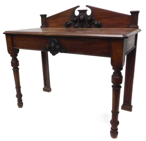 A Victorian mahogany hall or serving table, the raised back mounted centrally with a cartouche and leaves, the rectangular top with canted corners and edge, above a plain frieze, decorated centrally with scrolls, etc., on turned tapering legs, 109cm high