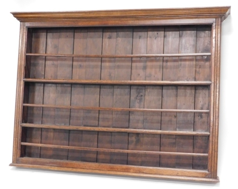 A late 18th/early 19thC oak plate rack, with a moulded cornice above three plate shelves each with a separate rail, flanked by channelled sides, 128cm high, 178cm wide.