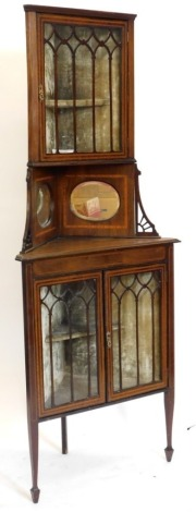 An Edwardian mahogany and satinwood crossbanded standing corner cabinet, the top with a glazed door enclosing a fitted interior, above two part mirrored supports each with pierced brackets, the base with two glazed doors enclosing a fitted interior on squ