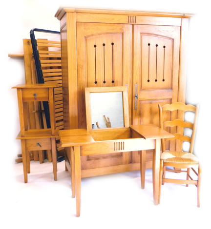 A French pine bedroom suite, comprising two door wardrobe with pierced panelled doors, enclosing shelves, a double bed head and foot, a dressing table with hinged central section, and a pair of bedside tables, each with two drawers and associated beech ch