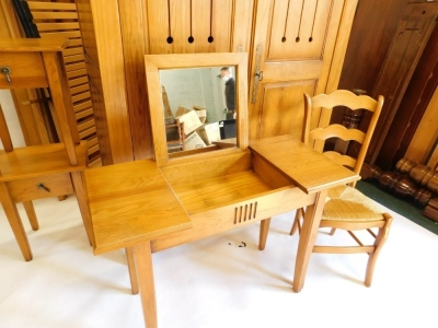 A French pine bedroom suite, comprising two door wardrobe with pierced panelled doors, enclosing shelves, a double bed head and foot, a dressing table with hinged central section, and a pair of bedside tables, each with two drawers and associated beech ch - 3
