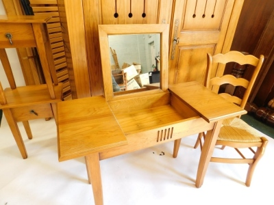 A French pine bedroom suite, comprising two door wardrobe with pierced panelled doors, enclosing shelves, a double bed head and foot, a dressing table with hinged central section, and a pair of bedside tables, each with two drawers and associated beech ch - 4
