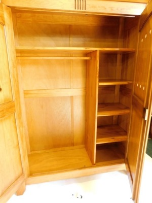 A French pine bedroom suite, comprising two door wardrobe with pierced panelled doors, enclosing shelves, a double bed head and foot, a dressing table with hinged central section, and a pair of bedside tables, each with two drawers and associated beech ch - 5