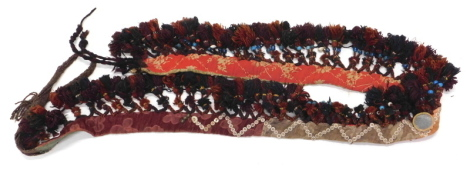 A Persian type horse collar, with a woven carpet band, long tassels, etc., 80cm x 15cm.