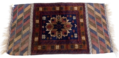 A Belouch rug, with a central medallion, in brown and cream, on a navy ground with multiple borders and flat weave ends, 160cm x 85cm.
