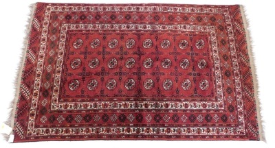 A Bokhara rug, with a typical design of three rows of medallions on a red ground, with multiple borders, 220cm x 140cm.