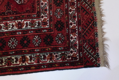 A Bokhara rug, with a typical design of three rows of medallions on a red ground, with multiple borders, 220cm x 140cm. - 2