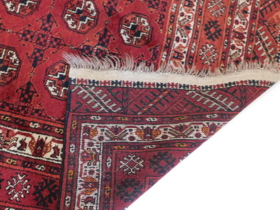 A Bokhara rug, with a typical design of three rows of medallions on a red ground, with multiple borders, 220cm x 140cm. - 3