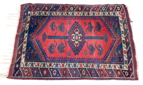 A Persian rug, with a pole medallion on a red ground with one wide and one narrow border.
