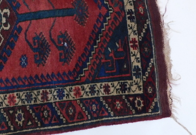 A Persian rug, with a pole medallion on a red ground with one wide and one narrow border. - 2