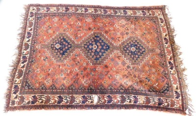 An Afshar carpet, with an all over design of roundels, flowers, and other geometric devices, on a red ground, with multiple borders, 210cm x 150cm.