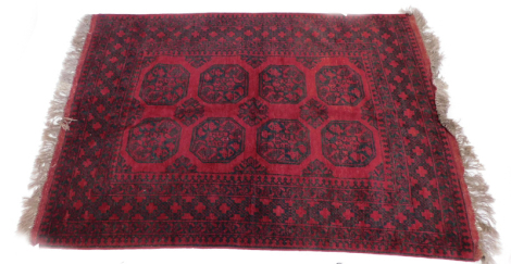 An Afghan rug, with an all over design of medallions, etc., in navy, on a red ground.