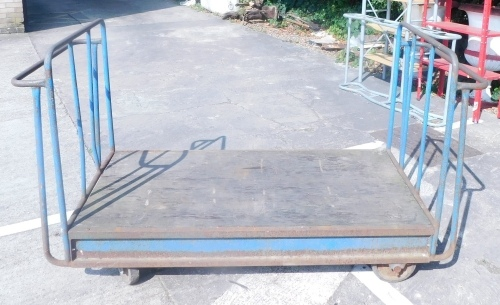 A blue painted tubular metal industrial four wheel trolley.