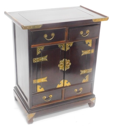 A Chinese hardwood and brass side cabinet, with a shaped top above two frieze drawers and two doors, each with strap hinges and two further drawers, on bracket feet, 82cm high, 69cm wide.